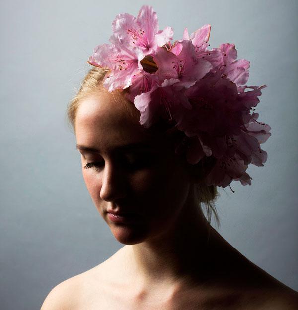 Portrætfoto af kvinde med lyserøde blomster i håret